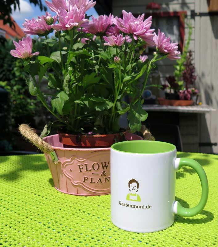 Die Gartenmoni Tasse auf dem Gartentisch